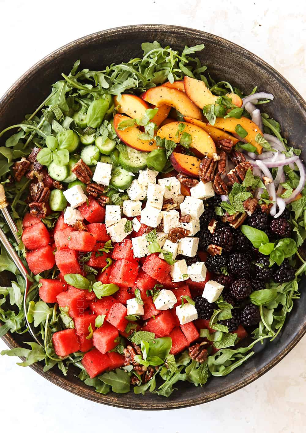 showing how to make watermelon salad recipe by adding watermelon, feta, mint, arugula, cucumbers and berries to a large bowl