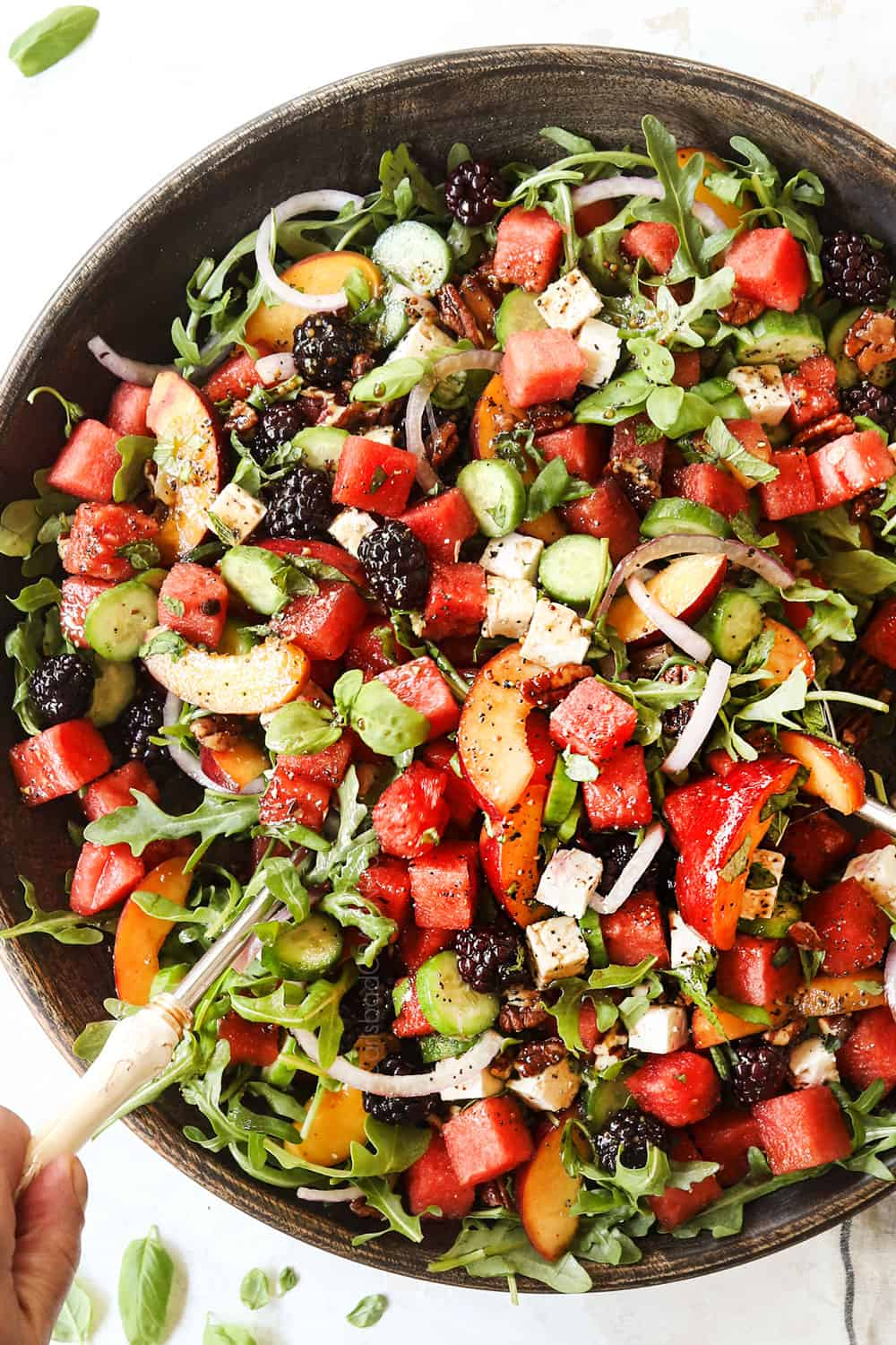 showing how to make watermelon salad recipe by tossing salad together in a large bowl