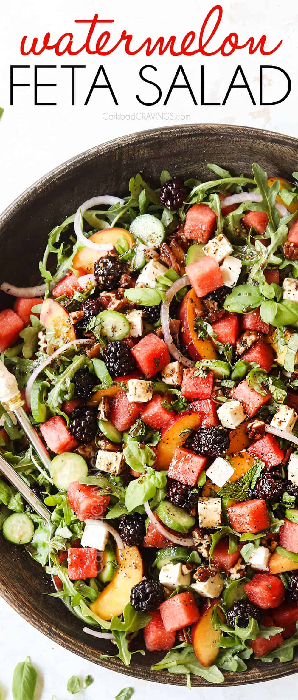 top view of a large serving bowl of watermelon salad with feta, basil, mint, cucumbers and arugula