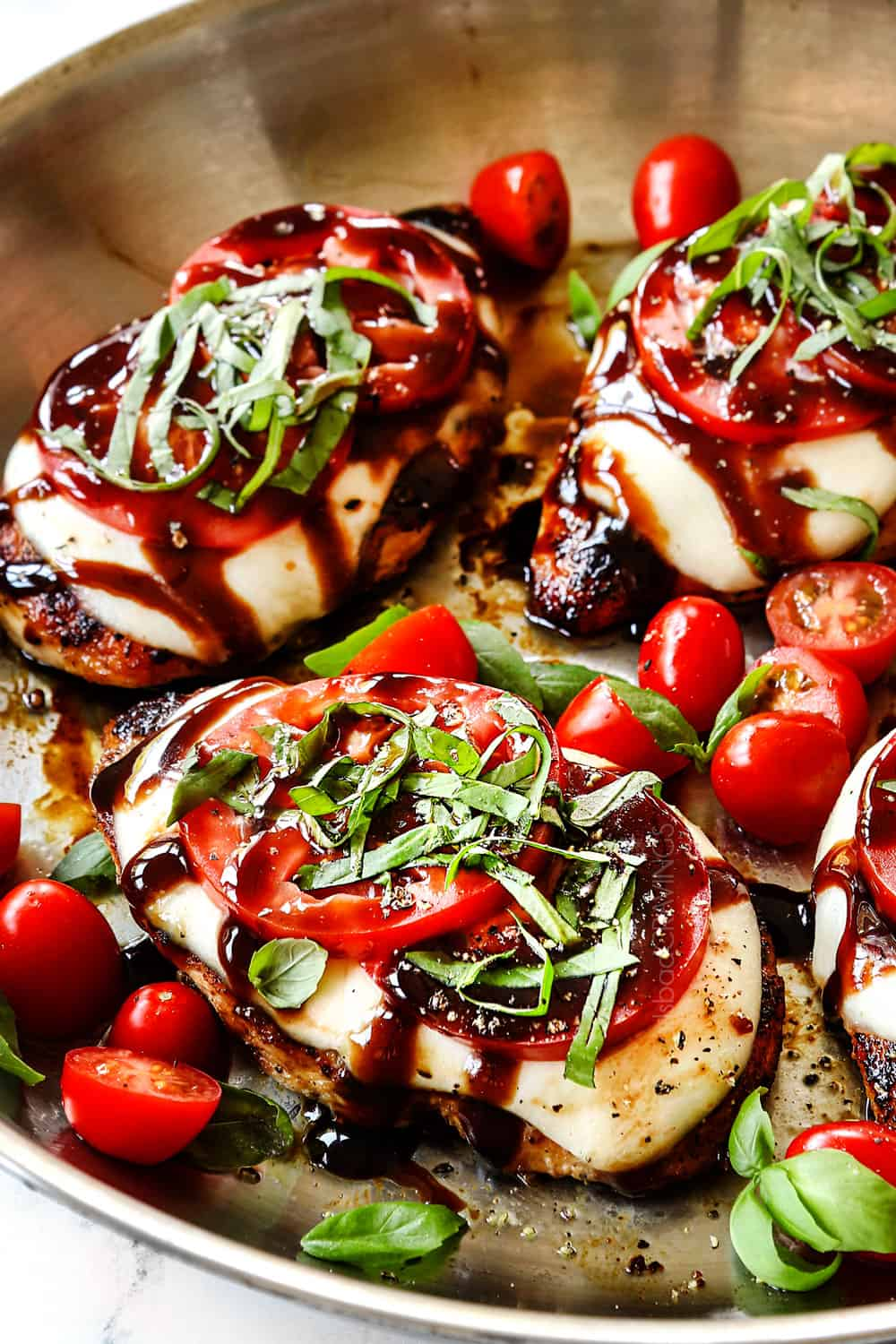 up close showing how to make chicken Caprese by adding basil to chicken on top of the tomatoes in a stainless steel skillet