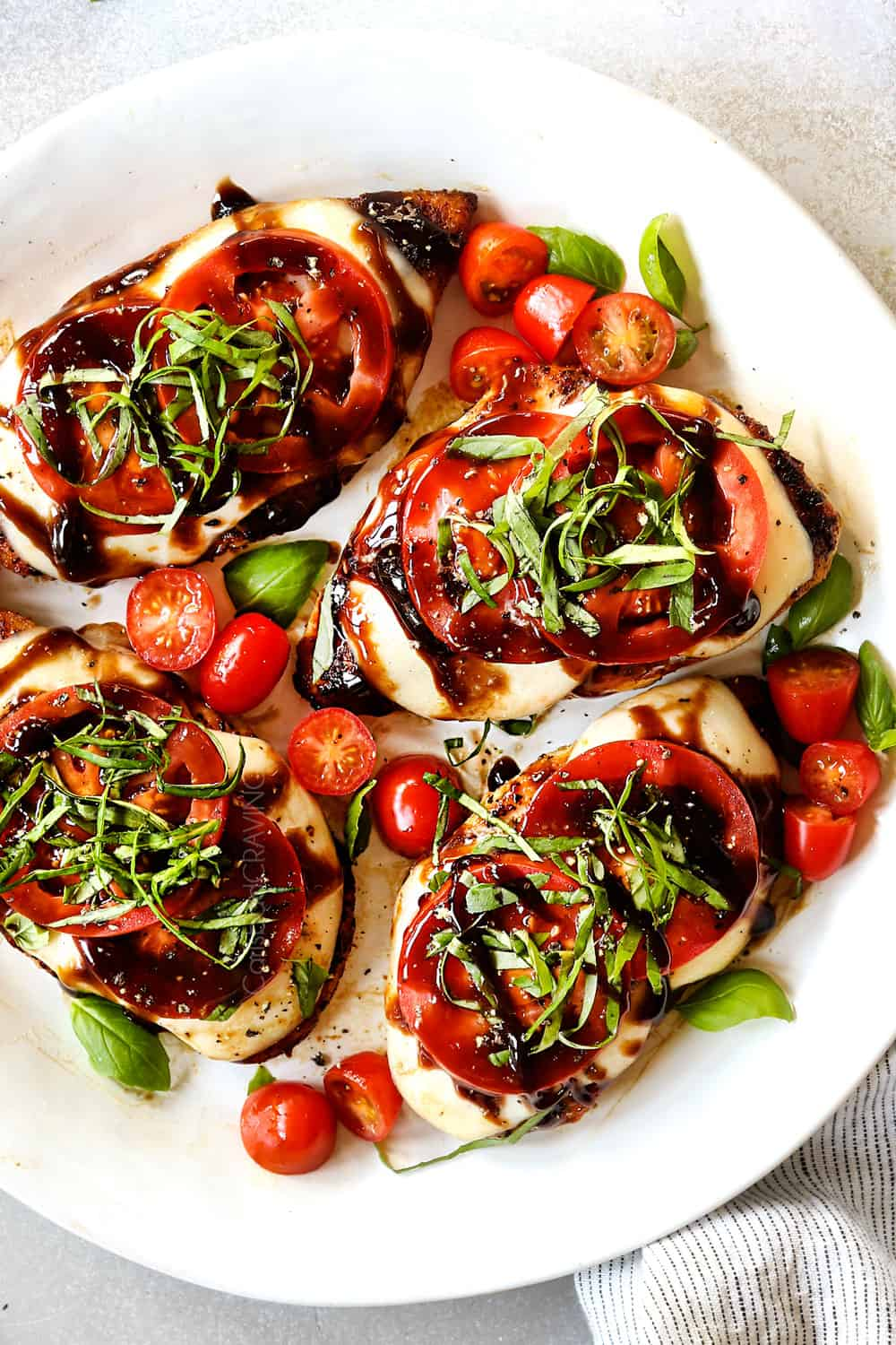 showing how to serve chicken Caprese recipe by adding chicken to a serving platter and drizzling with balsamic glaze