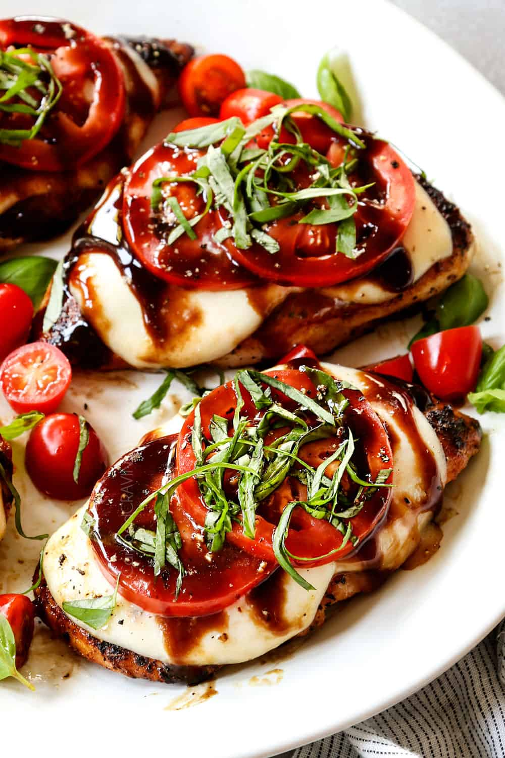 up close of chicken caprese recipe being served on a white plate with mozzarella, tomatoes, basil and balsamic reduction (balsamic glaze)