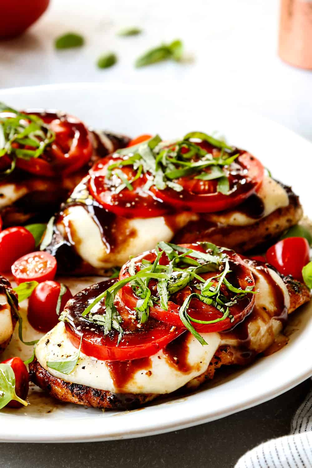 up close of chicken Caprese showing how cheesy it is layered with mozzarella cheese, tomato slices, basil and balsamic reduction