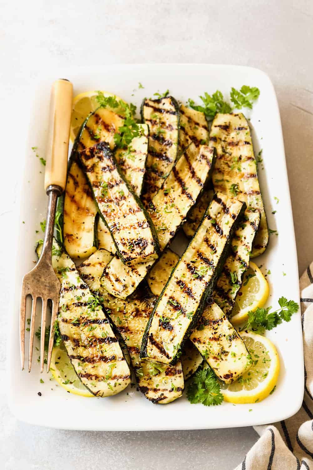 front view of grilled zucchini recipe garnished by lemon