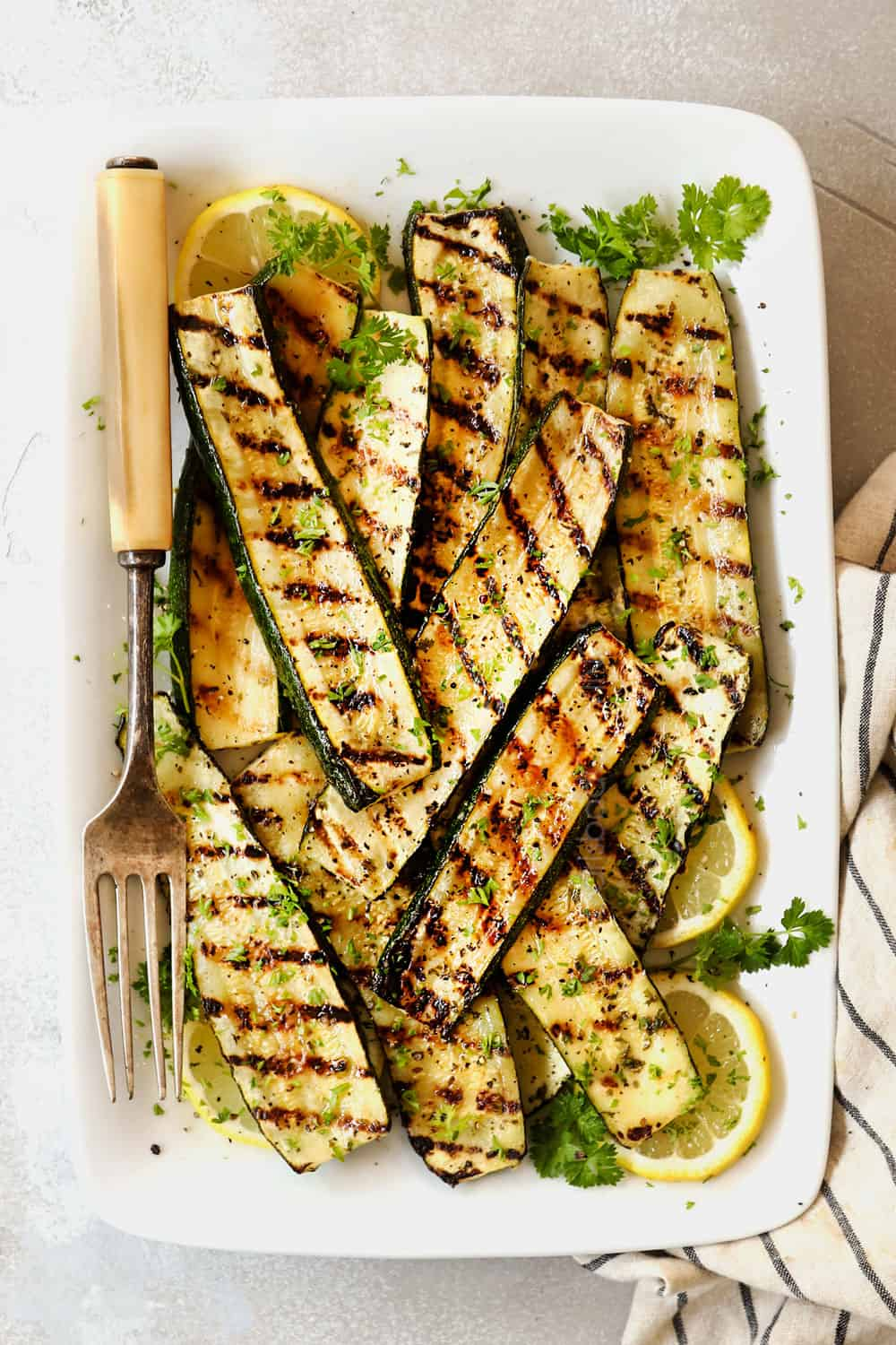top view of grilled zucchini and squash on a white platter with distinct grill marks
