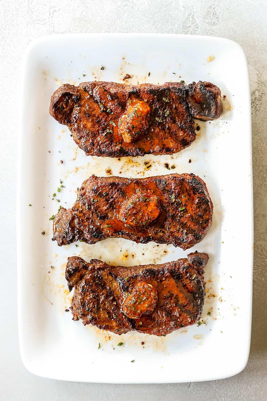 top view of New York Strip Steak (Strip Steak, NY Strip Steak) on a white platter with compound butter