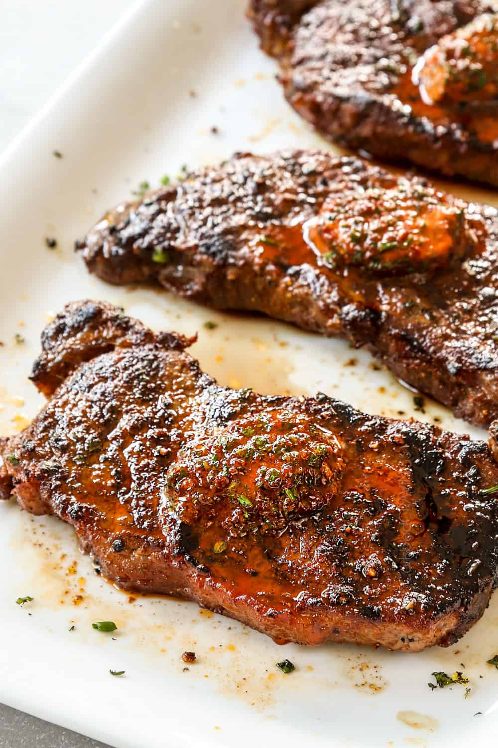 showing how to make New York Strip Steak (Strip Steak, NY Strip Steak) by adding compound butter to the top of the steaks