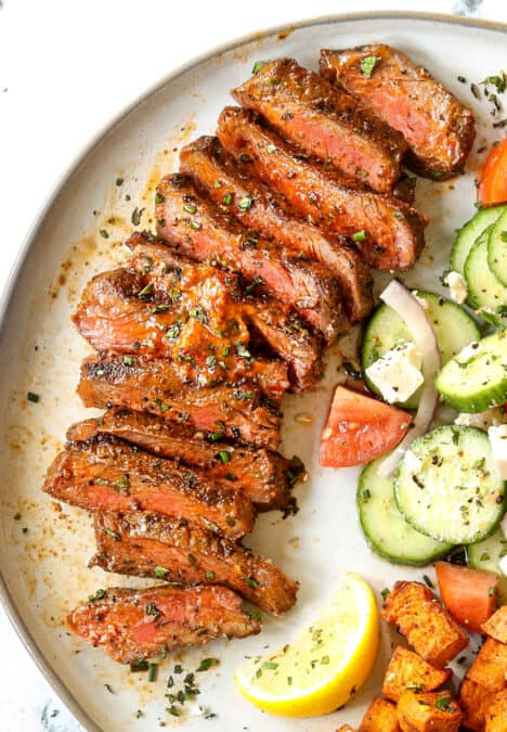 up close top view of New York Strip Steak (Strip Steak, NY Strip Steak) sliced on a plate with compound butter