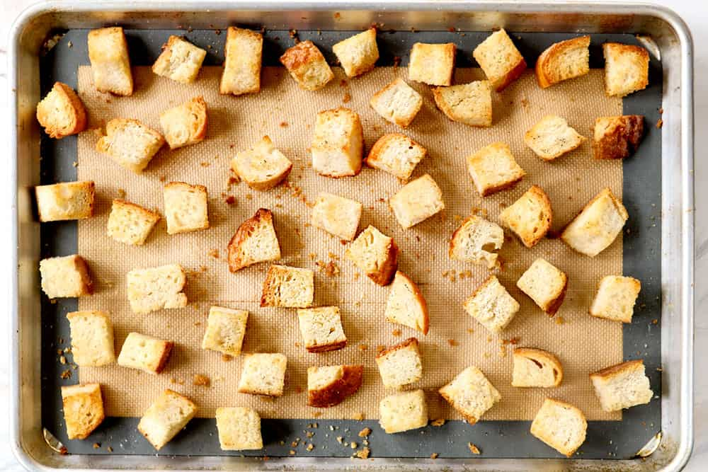 showing how to make Panzanella by toasting bread cubes on a baking sheet