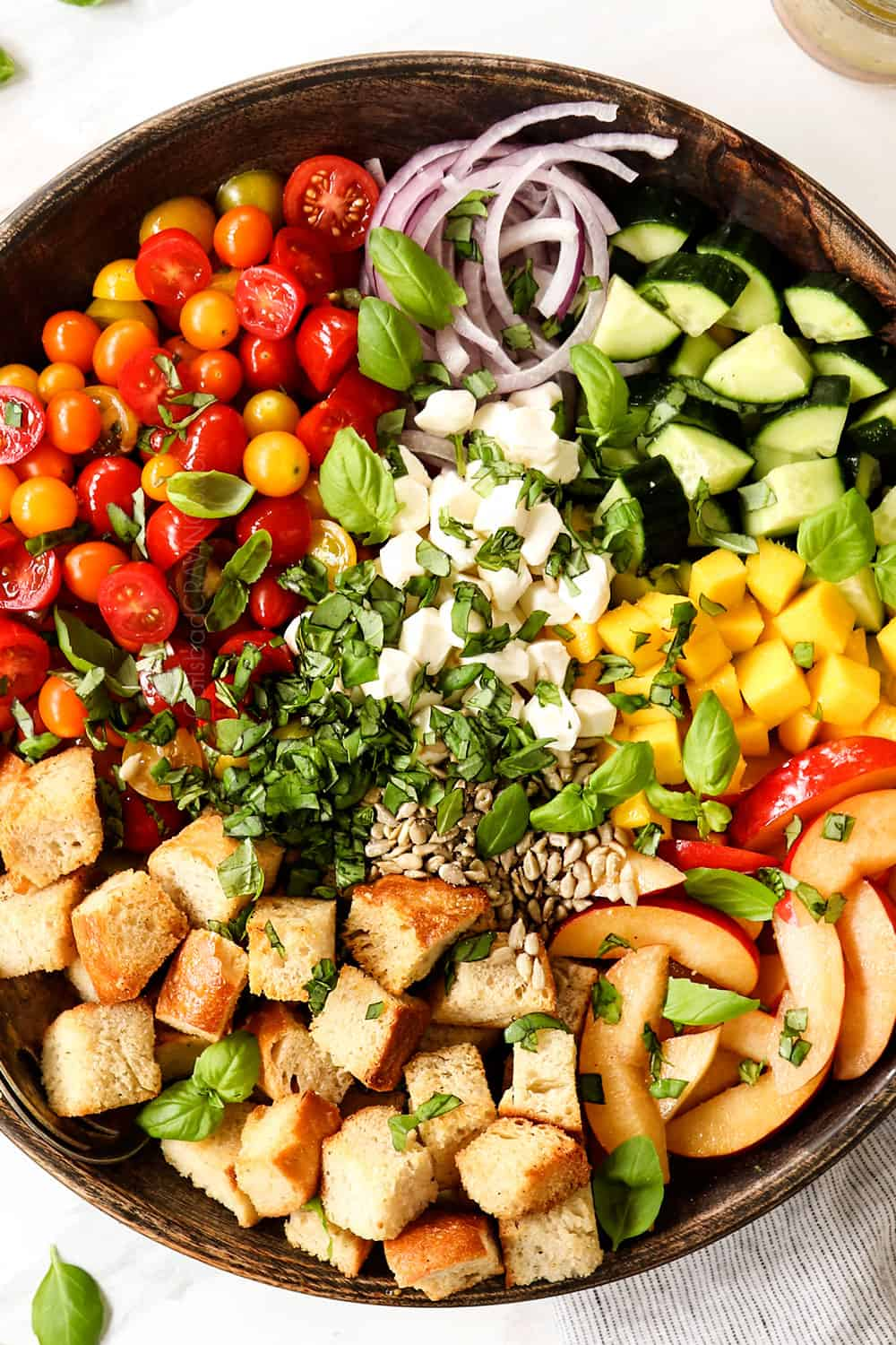 showing how to make Panzanella recipe by adding tomatoes, onions, cucumbers, bread, basil and mozzarella to a large serving bowl
