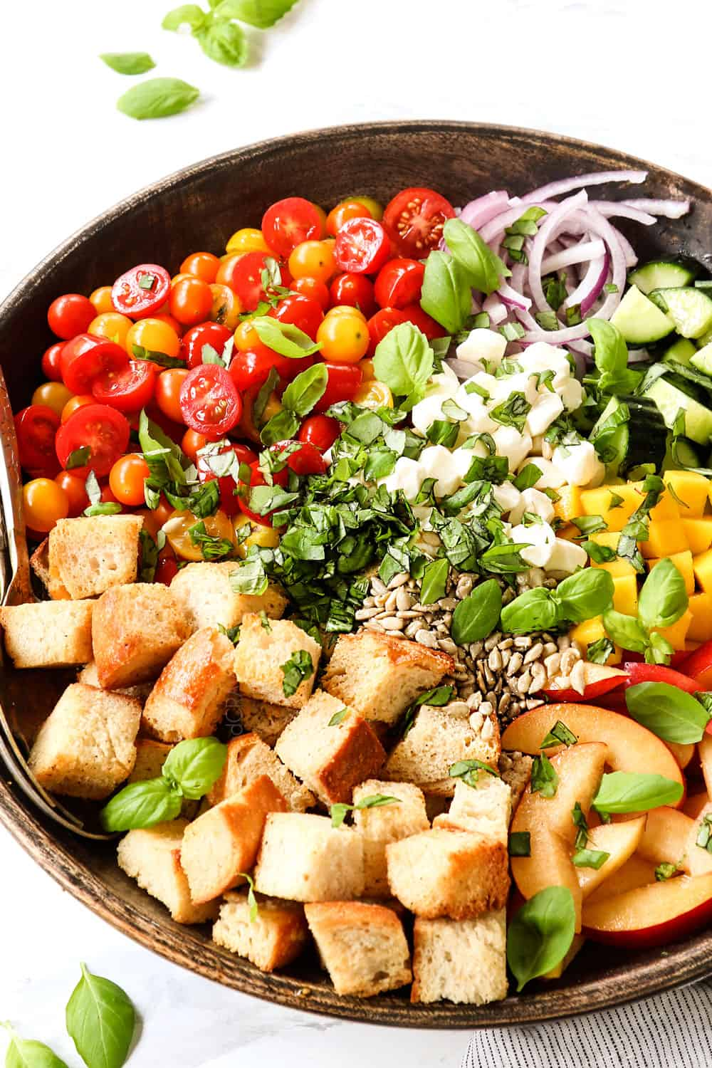 side view of showing how to make panzanella by adding the ingredients to a wood bowl:  cubed bread, tomatoes, onions, cucumbers and basil