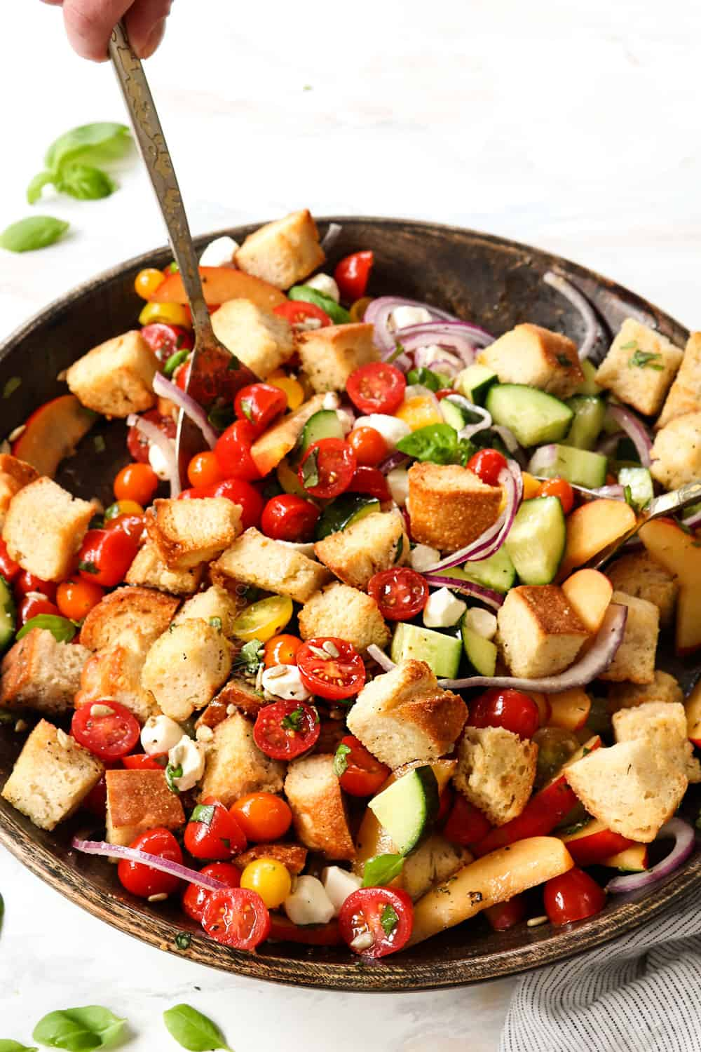 showing how to make Panzanella by tossing the bread, tomatoes and dressing in a wooden bowl