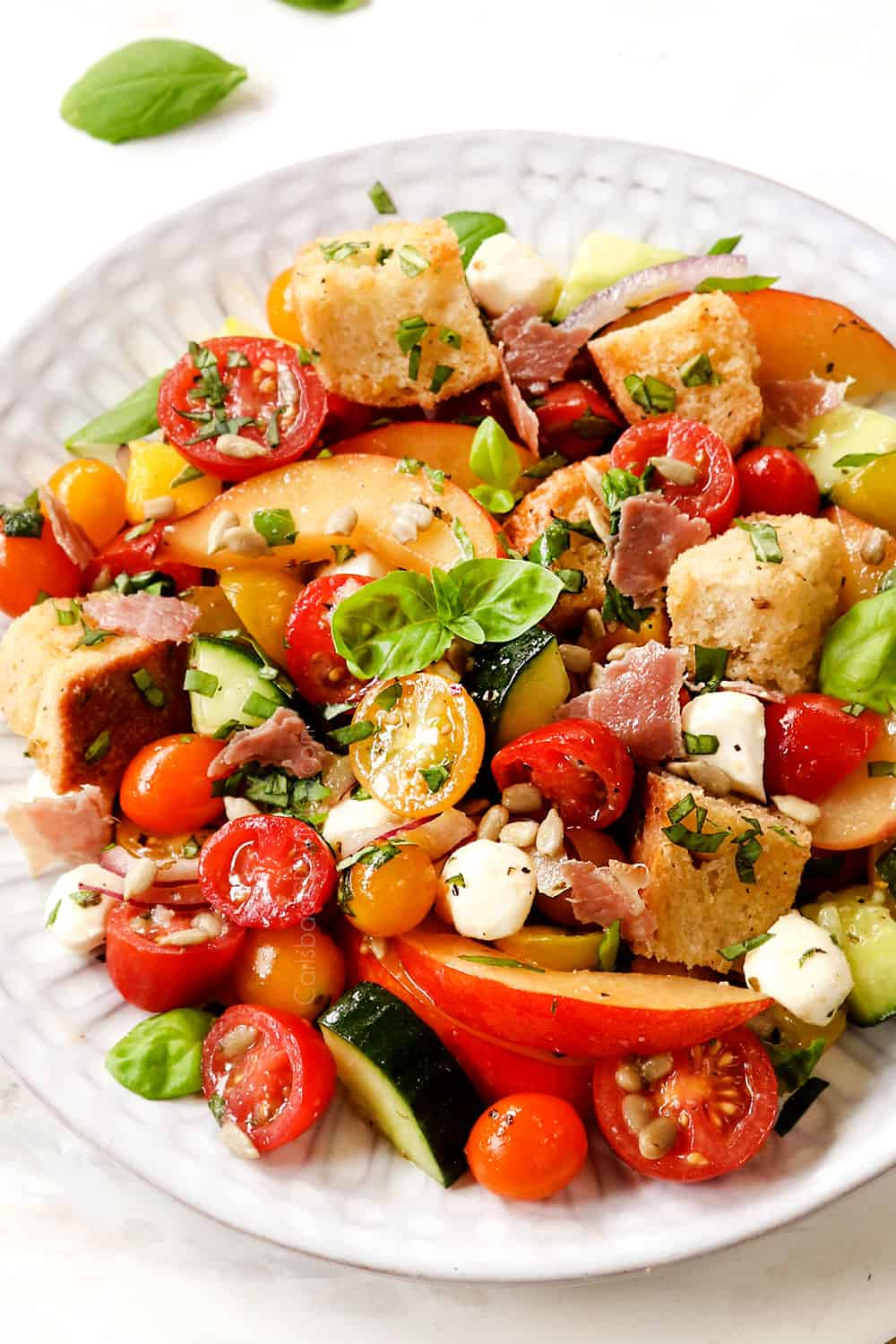 showing how how to serve panzanella salad recipe by adding to a plate and garnishing with fresh basil
