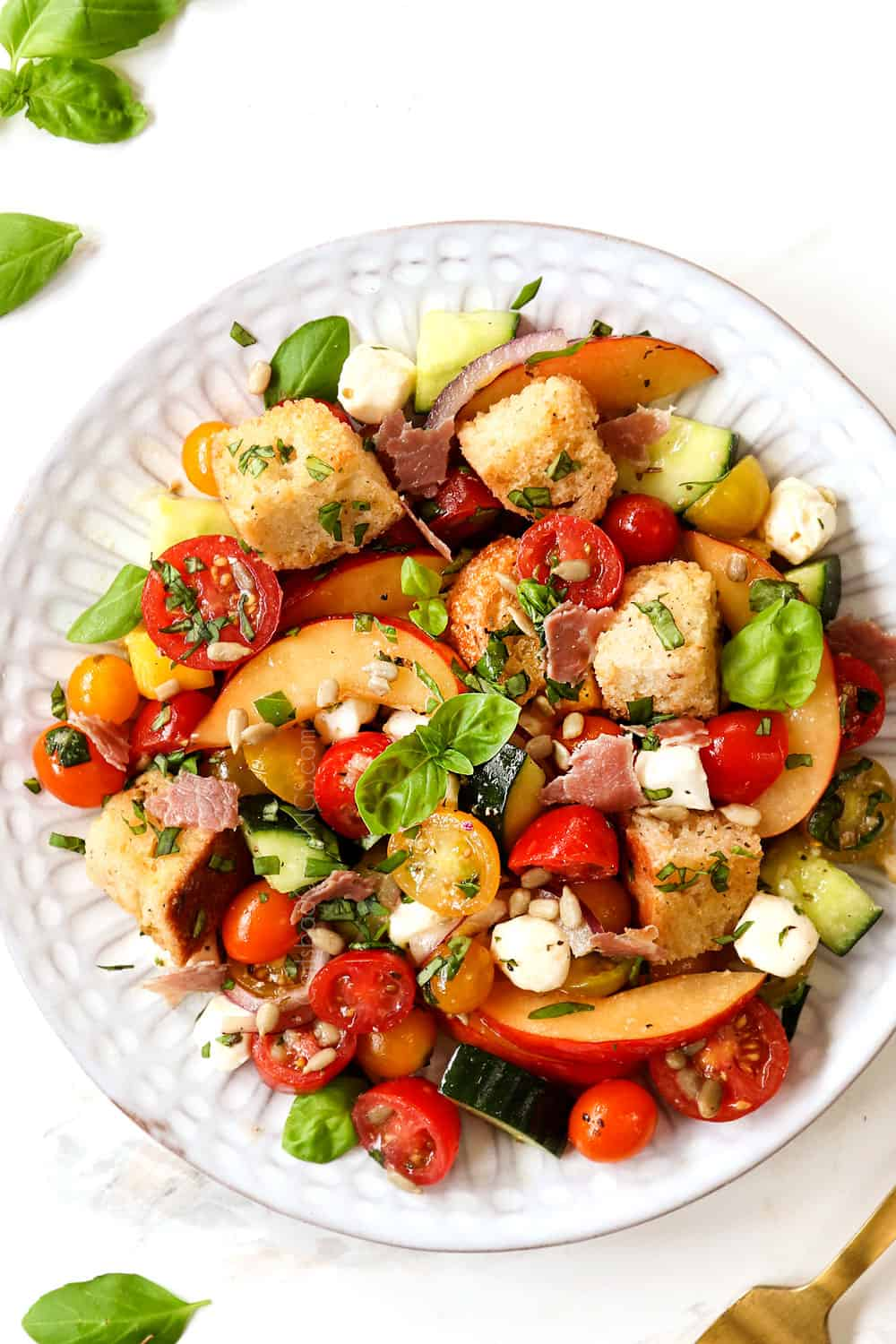 Panzanella salad on a white serving plate garnished with salt and pepper, soaked in red wine vinaigrette