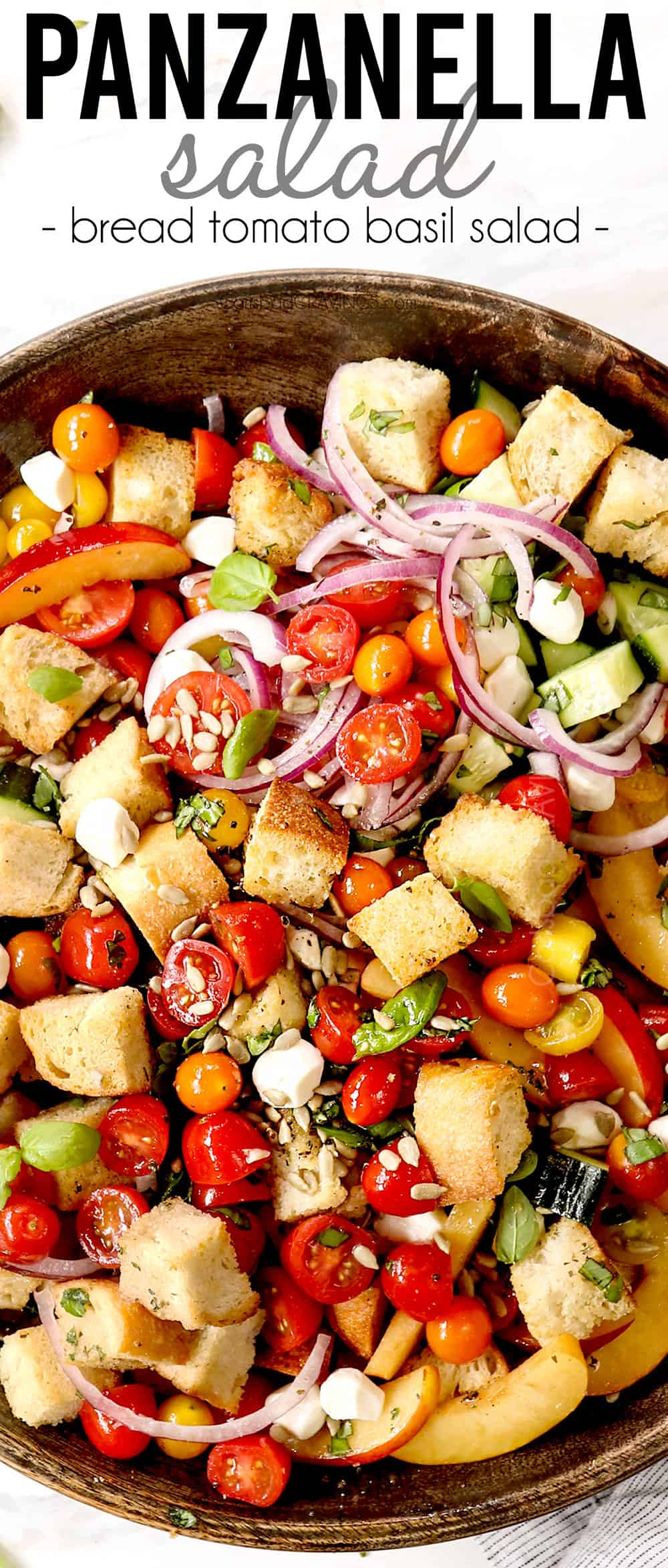 top view of panzanella in a wood serving bowl with tomatoes, red onions, cucumbers, basil, tomatoes and mozzarella