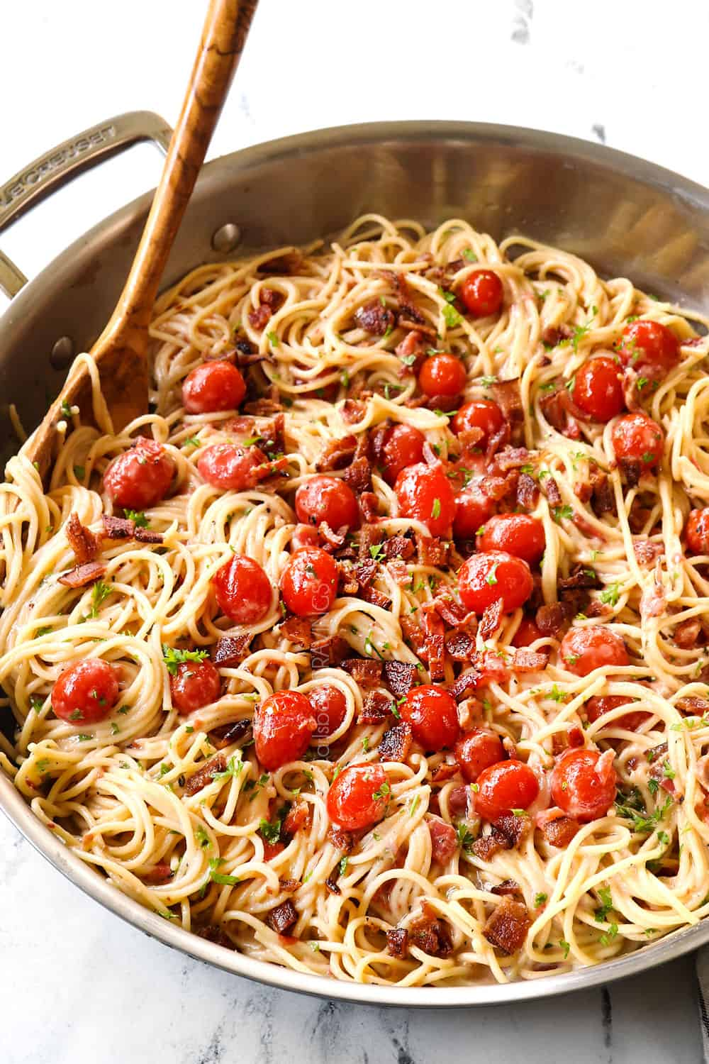 tomato bacon pasta in a skillet garnished by Parmesan