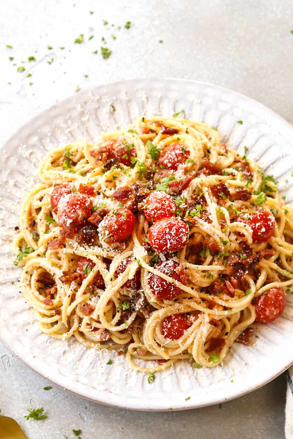 bacon pasta with tomatoes, garlic and Parmesan on a white plate