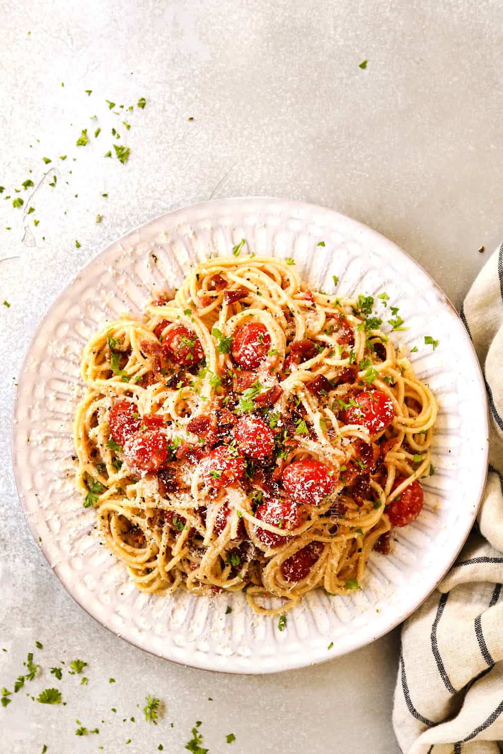 top view of bacon pasta with tomatoes, garlic and Parmesan on a white plate
