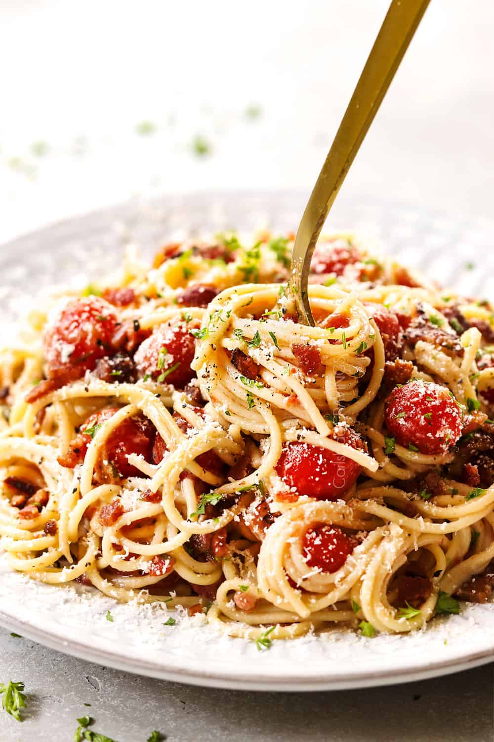 up close of a fork twirling tomato bacon pasta on a white plate