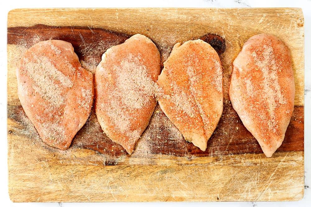 showing how to make blackened chicken recipe by seasoning chicken with blackening seasoning