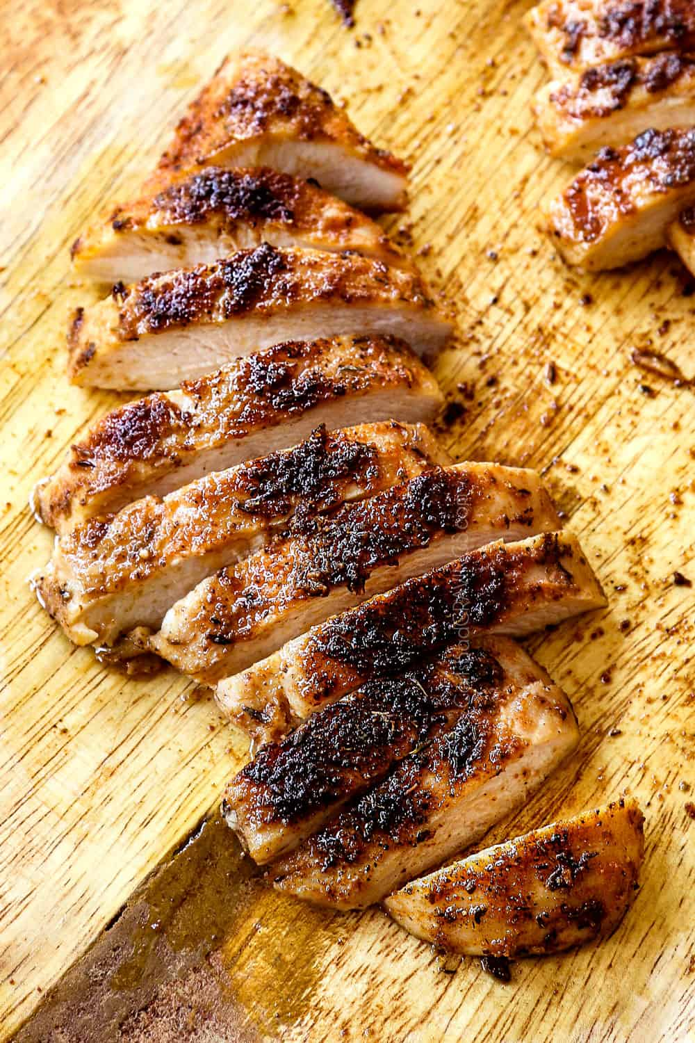 blackened chicken on a cutting board sliced into strips showing the charred crust