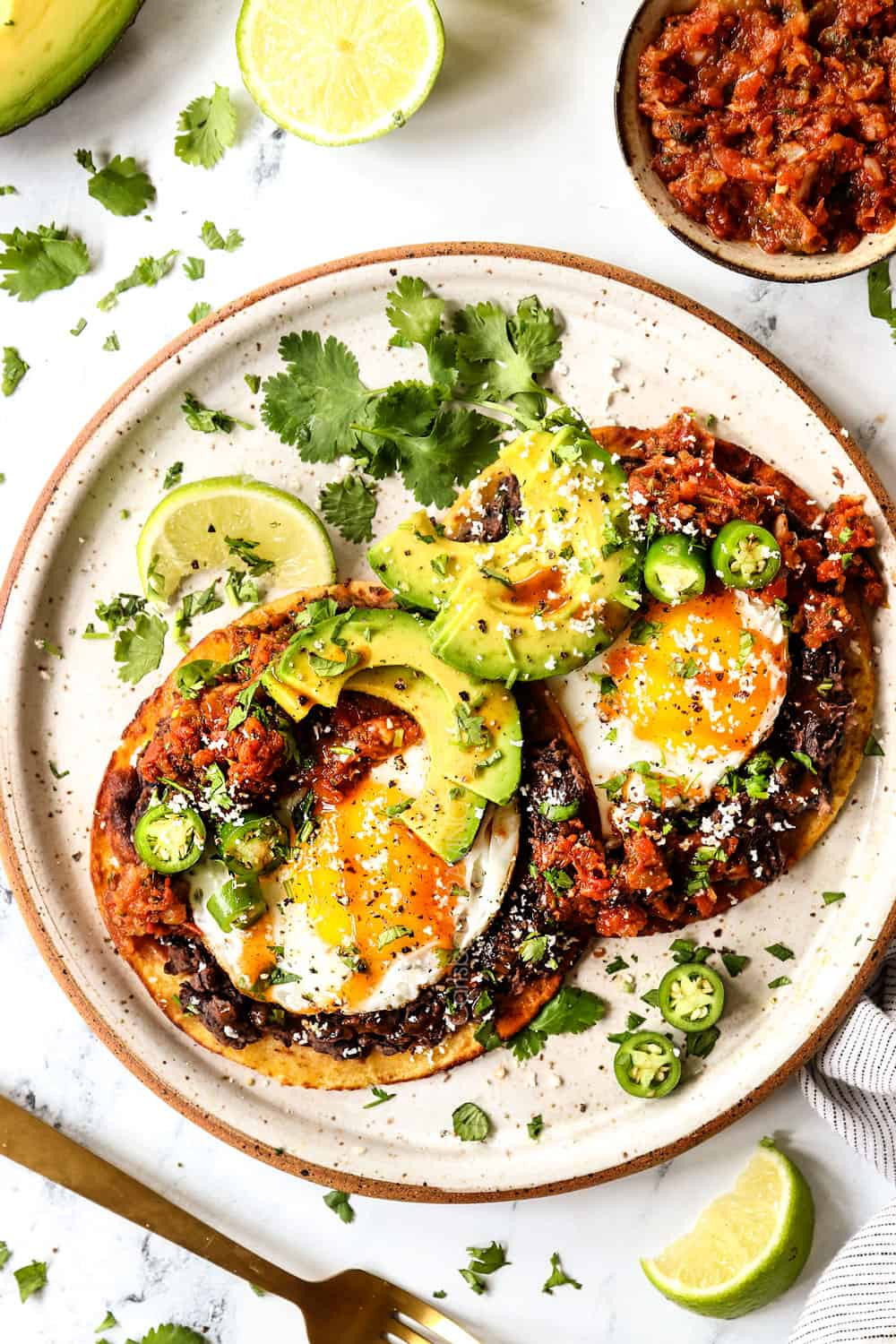 showing how to assemble Huevos Rancheros by adding refried beans, fried eggs, warmed salsa to a corn tortilla