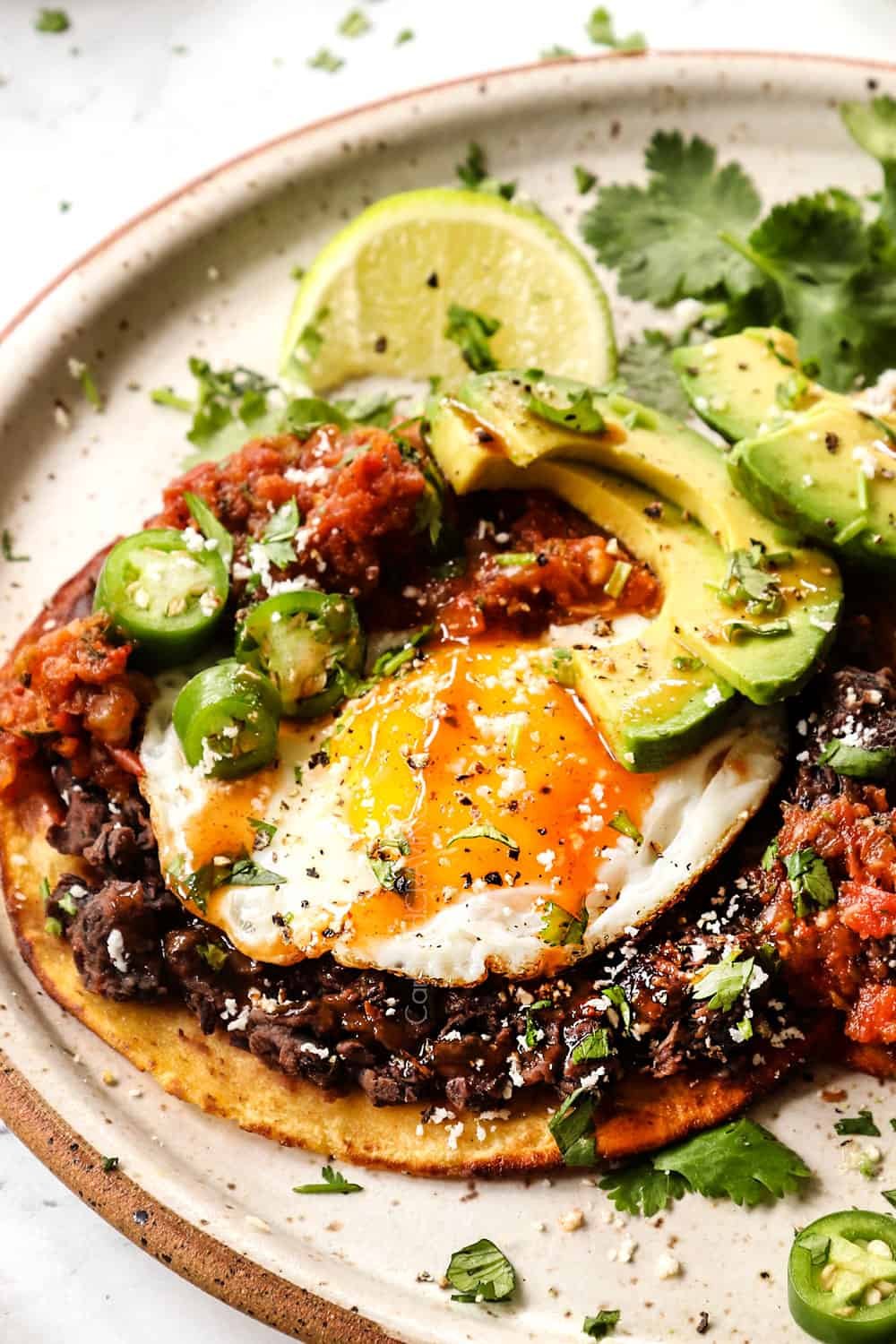 up close of Huevos Ranchers showing how to layer them: corn tortilla, refried beans, fried eggs, salsa and toppings of sliced avocado, Cotija cheese, cilantro and hot sauce