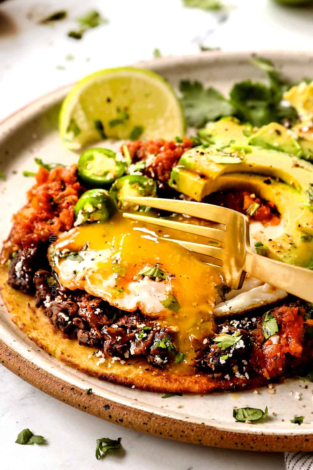 showing how to eat Huevos Rancheros by cutting the egg yolk so it runs into the salsa creating a sauce