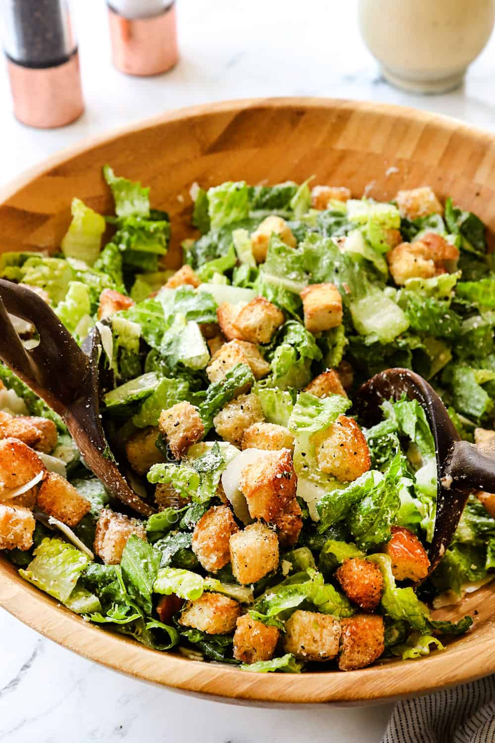 showing how to make Caesar Salad by tossing the ingredients together