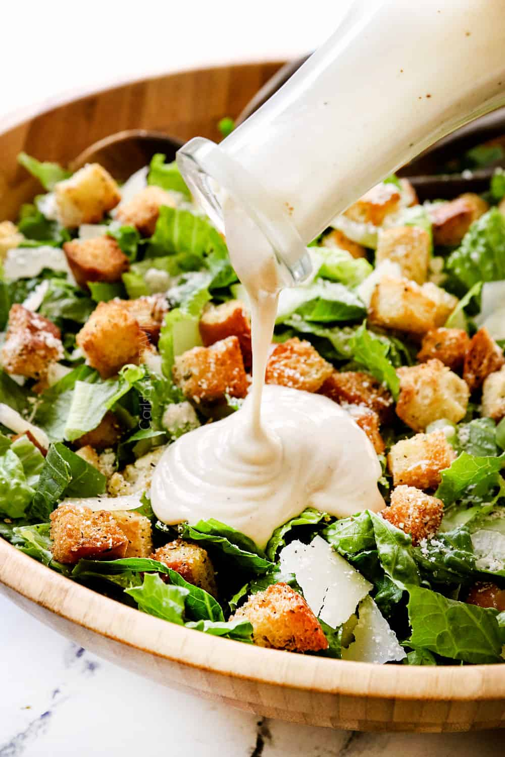 showing how to make Caesar Salad recipe by drizzling salad with Caesar Dressing