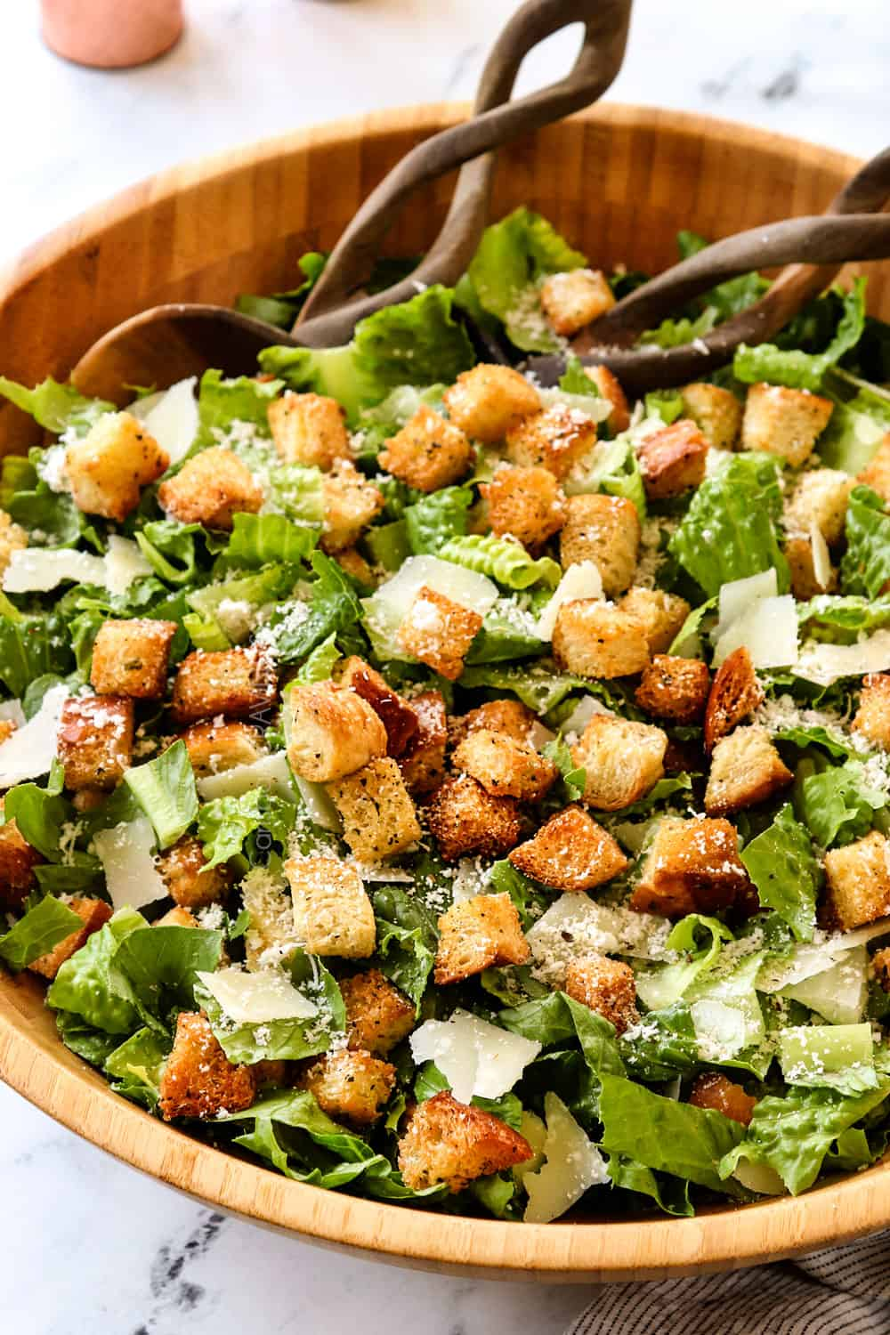 showing what's in Caesar Salad recipe by adding Romaine lettuce, croutons, Parmesan and homemade Caesar Dressing to a bowl