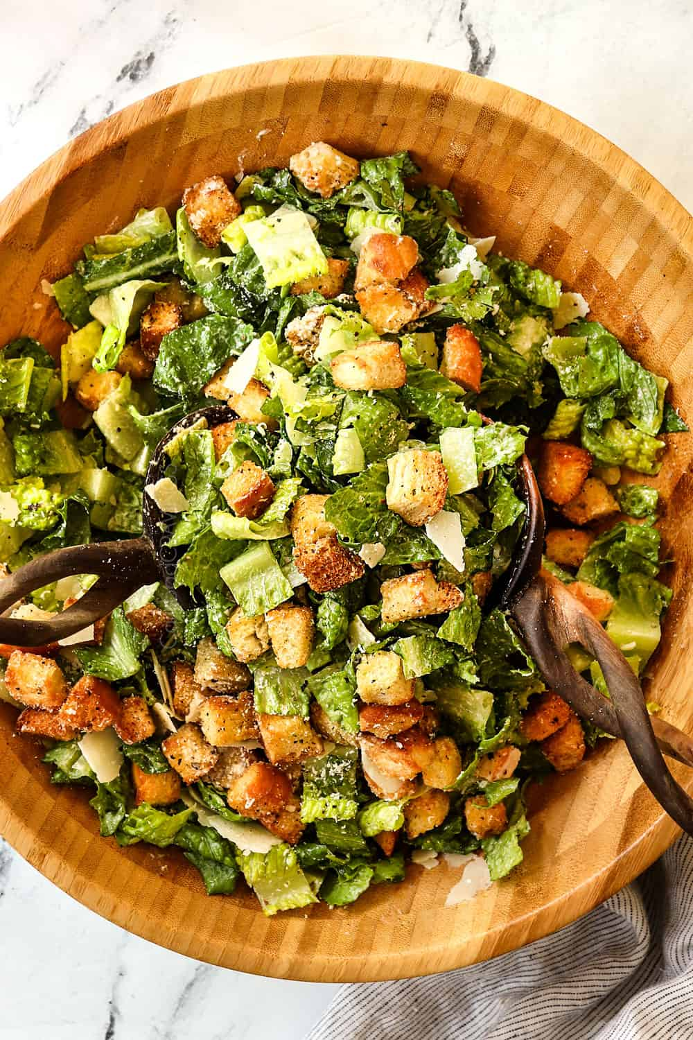 showing how to make Caesar Salad recipe by tossing the salad ingredients together in a wood bowl with tongs