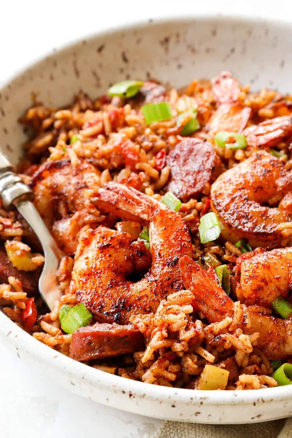 showing how to serve Cajun Shrimp and Rice by adding a serving to a bowl and garnishing with green onions
