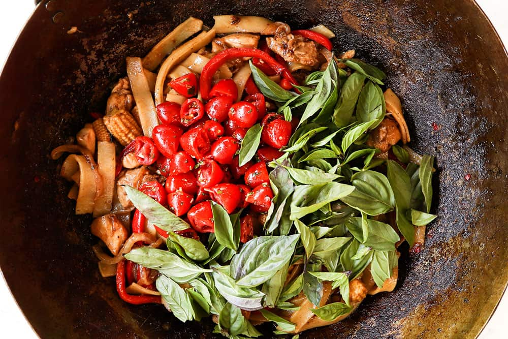 showing how to make Drunken Noodles (Pad Kee Mao) recipe by adding tomatoes, Thai basil to stir fried wide rice noodles