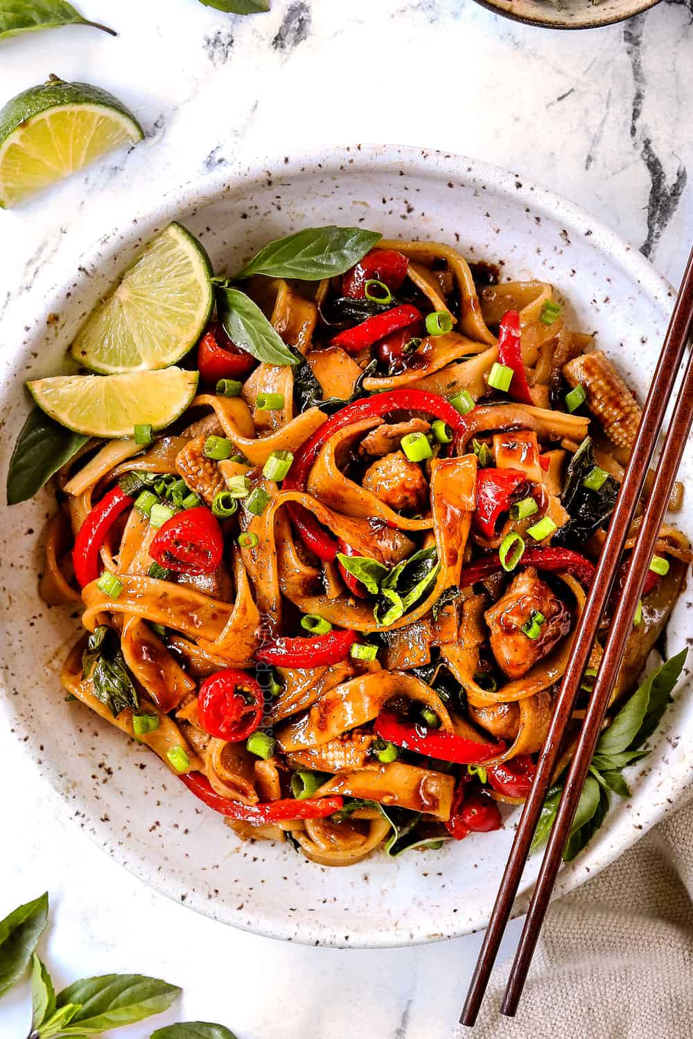 showing how to make Drunken Noodles (Pad Kee Mao) recipe by adding to a white bowl and garnishing with green onions and lime