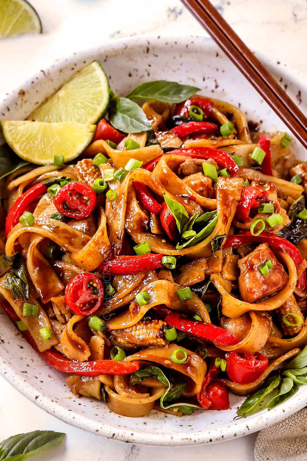 up close of Thai Drunken Noodles (Pad Kee Mao) in a white bowl with spicy and slightly sweet sauce with wide rice noodles