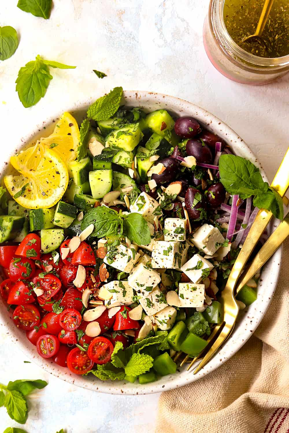 showing how to make Greek Salad by adding tomatoes, Kalamata olives, bell peppers, and feta to a bowl