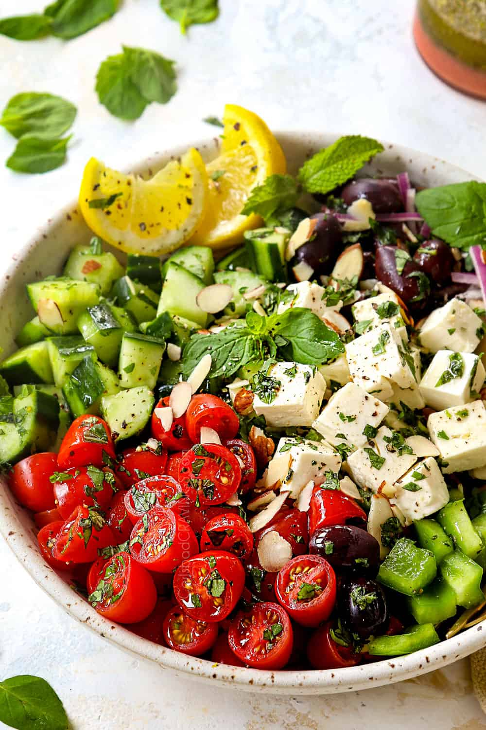 showing how to make Greek Salad by adding Greek Salad ingredients to a bowl: tomatoes, bell peppers, feta, cucumbers, red onions and Kalamata olives