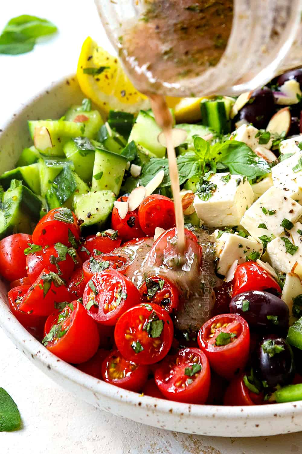 showing how to make Greek Salad by drizzling with Greek Salad Dressing