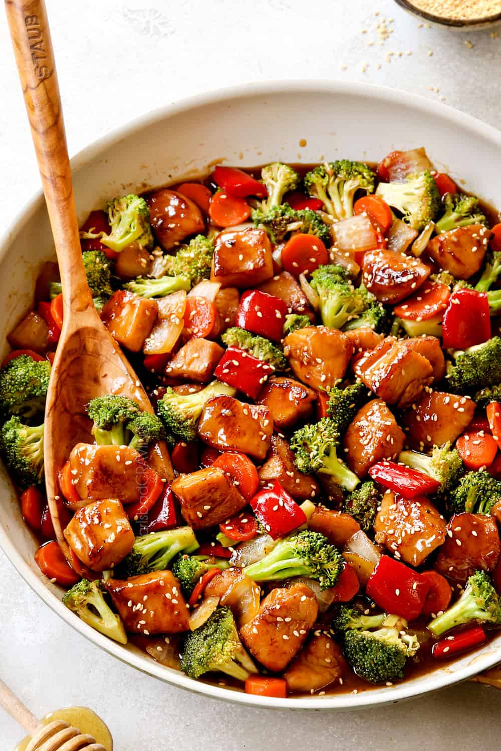 showing how to serve honey garlic chicken stir fry by garnishing with green sesame seeds in a skillet