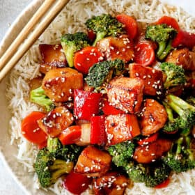 top view of Chinese honey garlic chicken served over rice garnished with sesame seeds