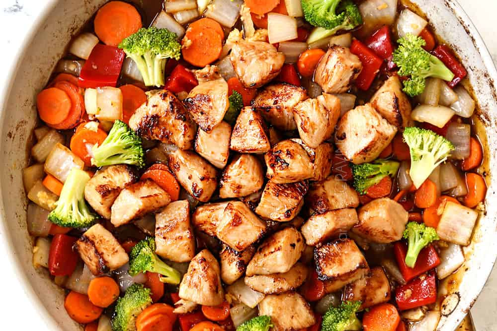 showing how to make honey garlic chicken stir fry recipe by adding chicken and sauce to the vegetables in the skillet