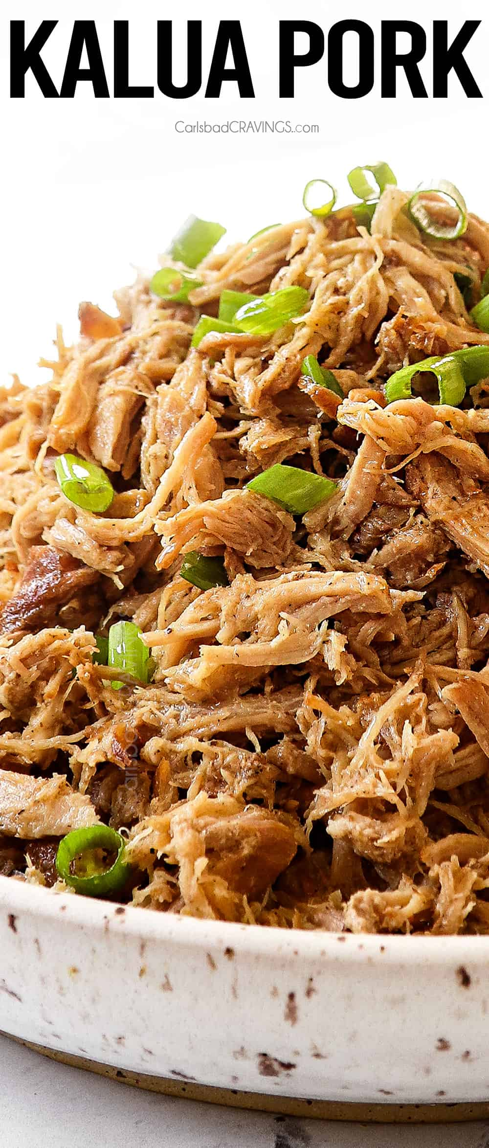 up close of a bowl of kalua pork garnished by green onions showing how tender and juicy it is
