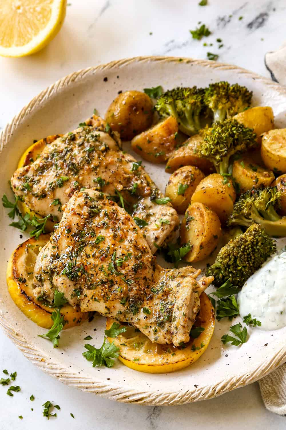 showing how to serve baked lemon garlic chicken thighs by serving on a plate with potatoes, broccoli and yogurt sauce