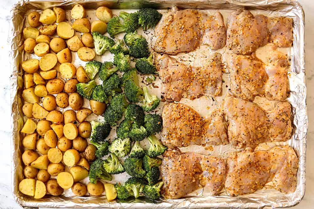 showing how to make lemon garlic chicken recipe by lining chicken thighs, broccoli and potatoes on a sheet pan to bake in the oven