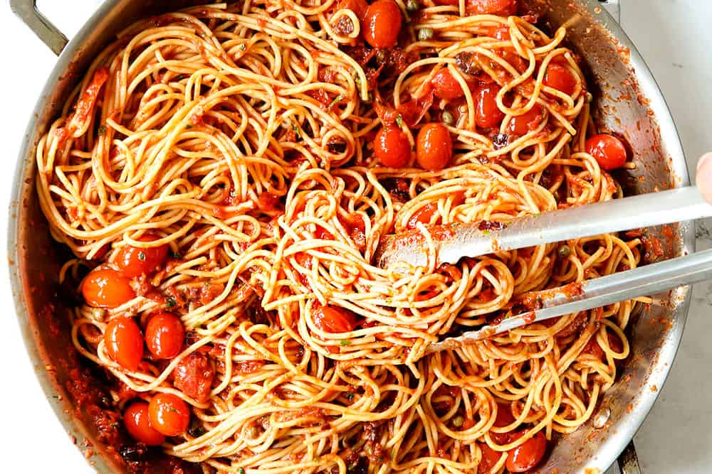 showing how to make Puttanesca recipe by stirring spaghetti into the Puttanesca sauce