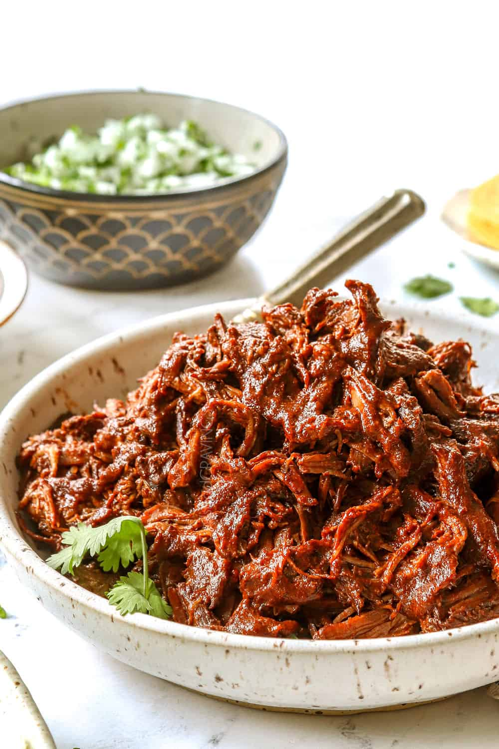 showing how to make birria recipe by adding shredded birria to a bowl