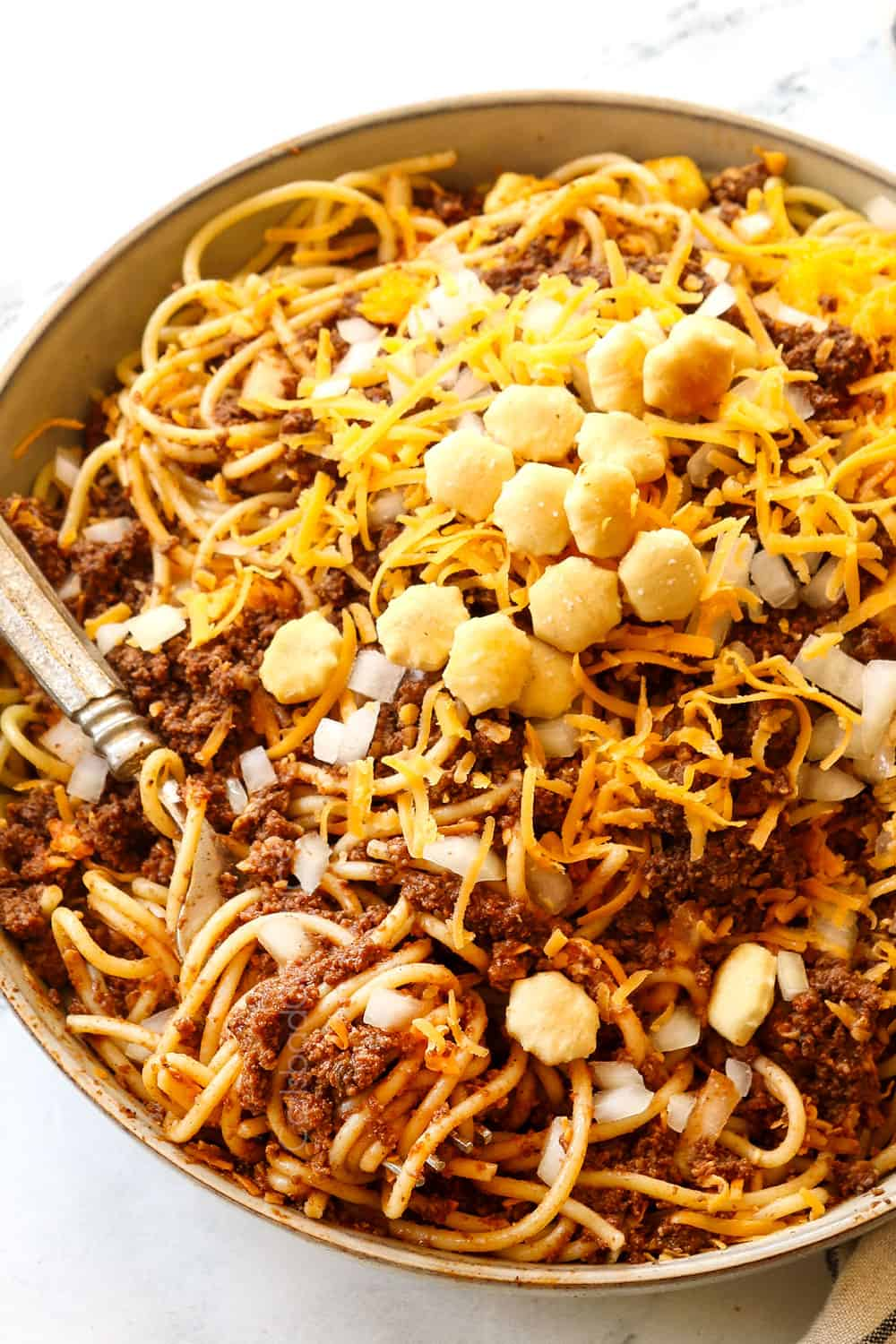 a fork digging into a bowl of Cincinnati chili showing how to eat it