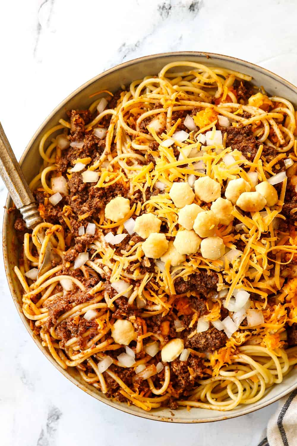 top view of Cincinnati chili served in a bowl over spaghetti with onions and cheese