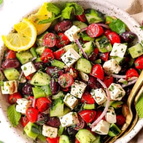 top view of showing how to make Greek Salad recipe by mixing tomatoes, cucumbers, Kalamata olives, red onions and feta together
